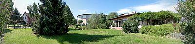 Haus Waldeck im malerischen Grün gelegen, im vorderen Bereich Wiesen, Bäume und Pflanzen vom Kaffee und Pavillon gefolgt und mit dem Rundbau des Pflegebereichs abschließend.